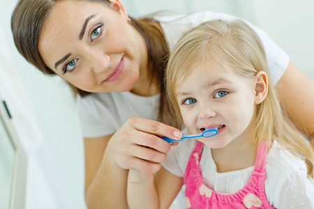 Mom and Daughter brushing their teeth - Pediatric Dentist in Memphis, TN